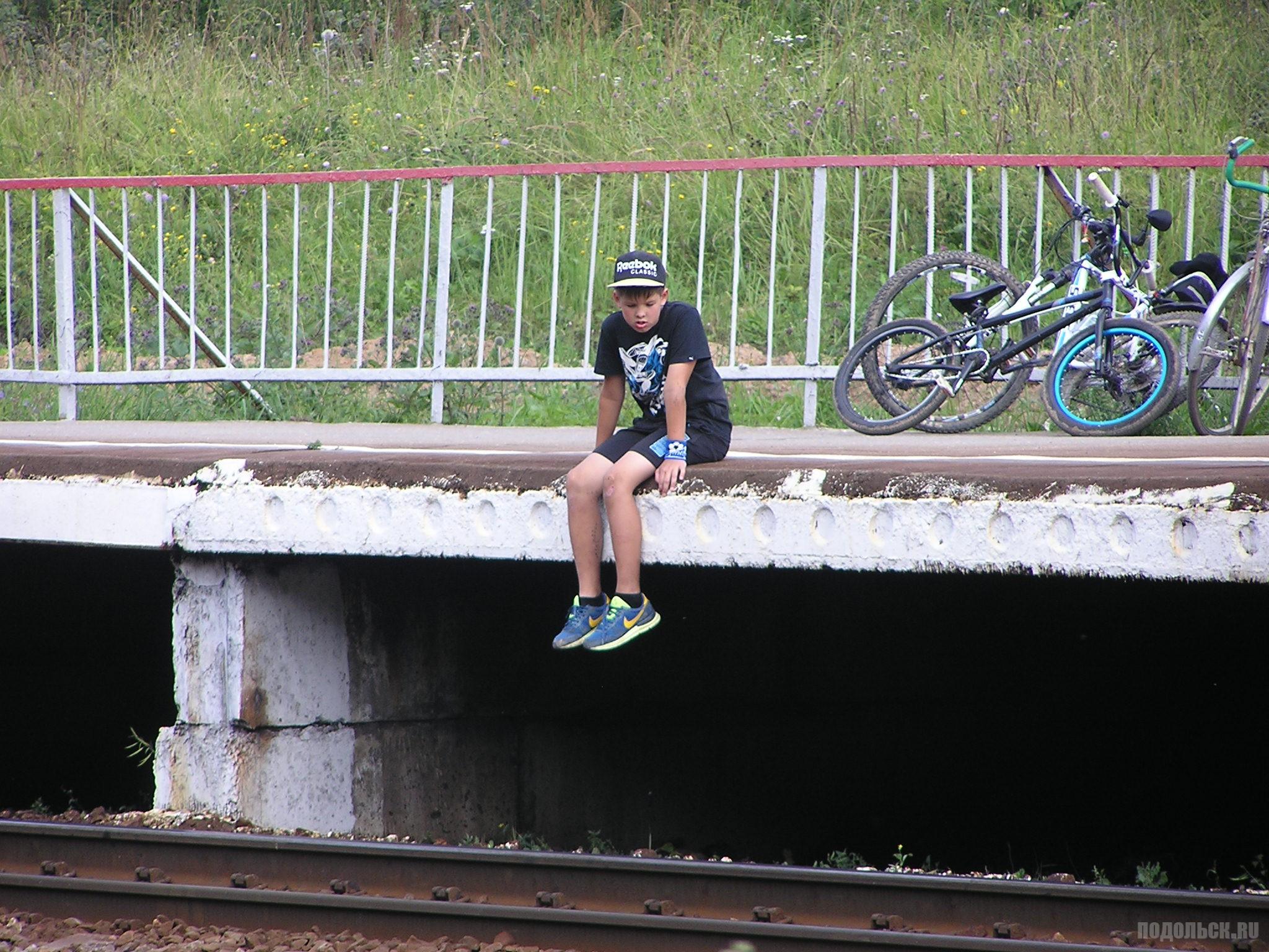 Мальчик сидит на краю платформы. Весенняя, 24 июля 2016 г.