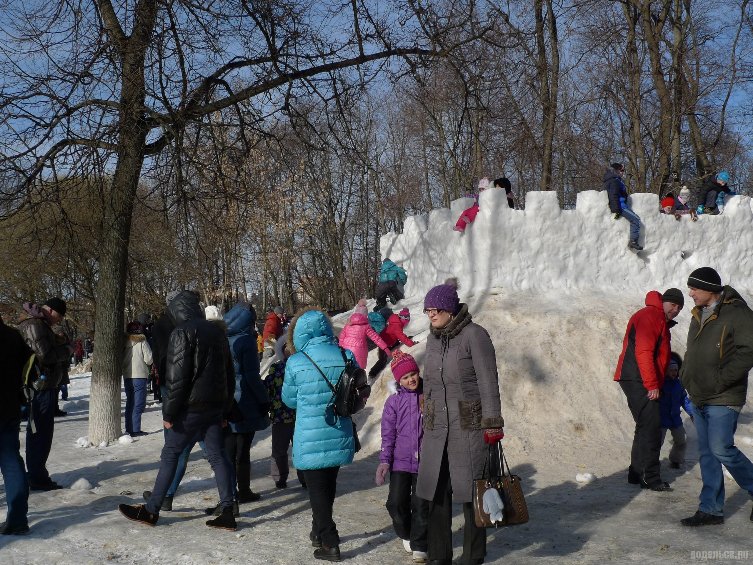Дети взбираются на горку. Масленица в центральном парке.